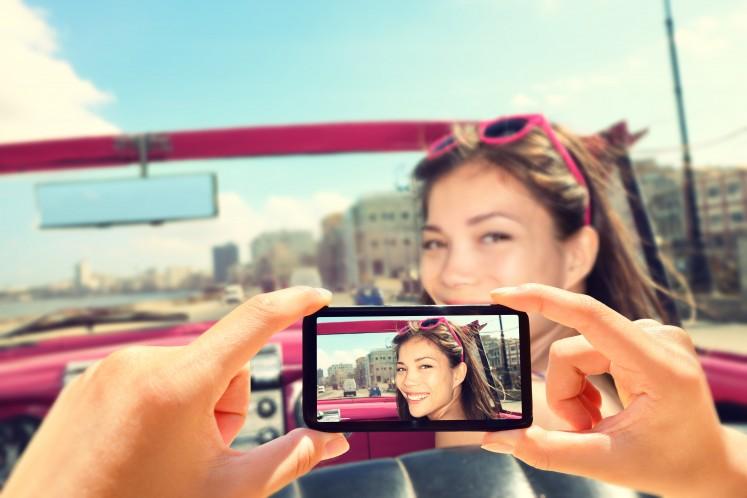 Woman_having_photo_taken_on_phone_in_car