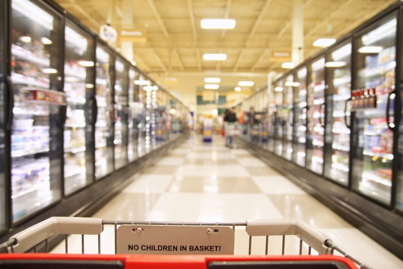A shopping trolley in a aisle in a grocery store showing frozen foods