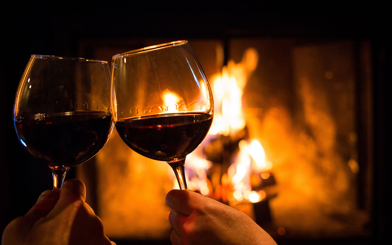 two glasses in front of a fire
